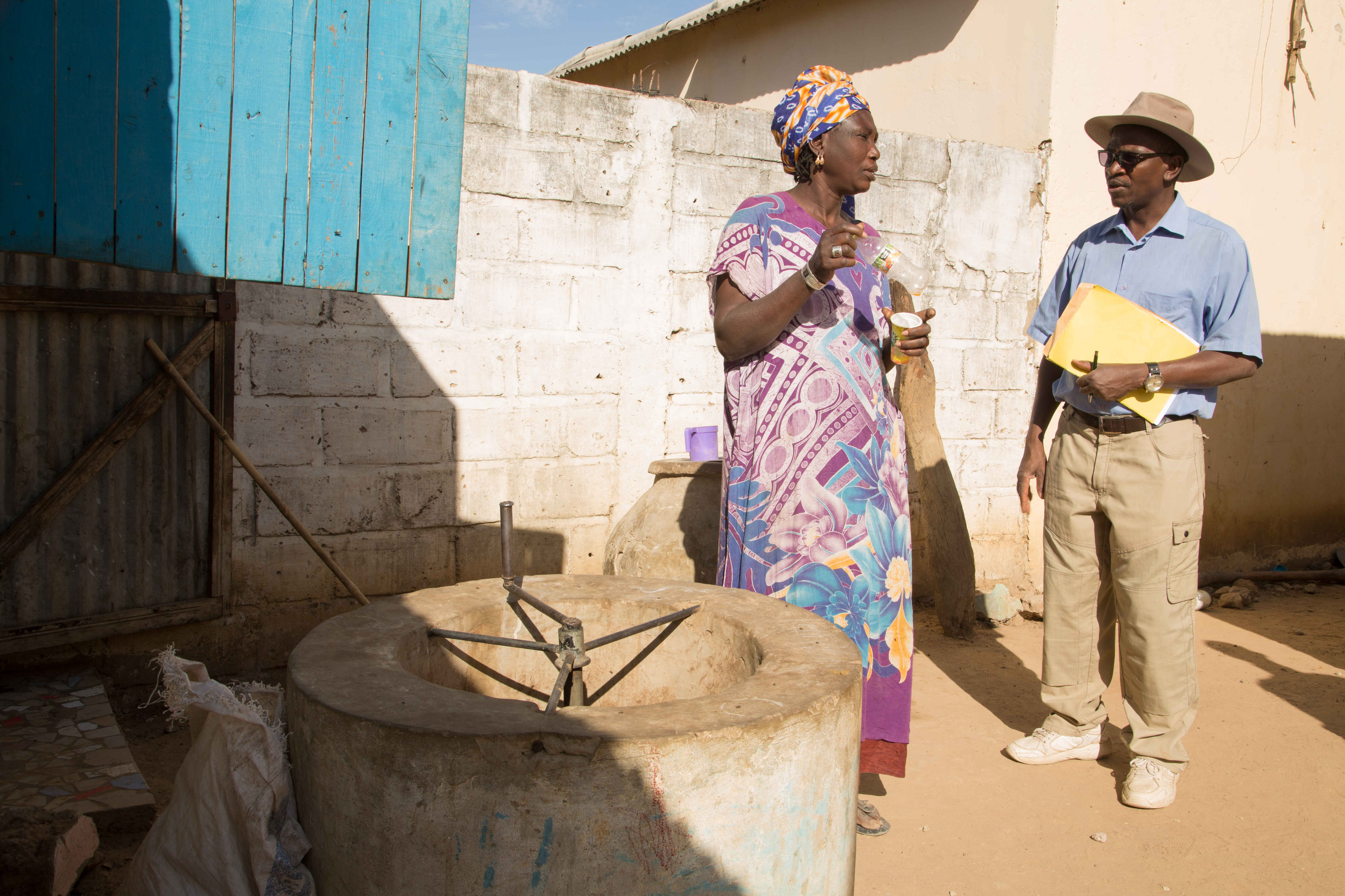 The woman in the colorful dress and headwrap talks to a man wearing sunglasses; a light blue, short-sleeved button-up; khaki pants; and a matching hat. They're standing near the biodigester in front of a short, white brick wall.