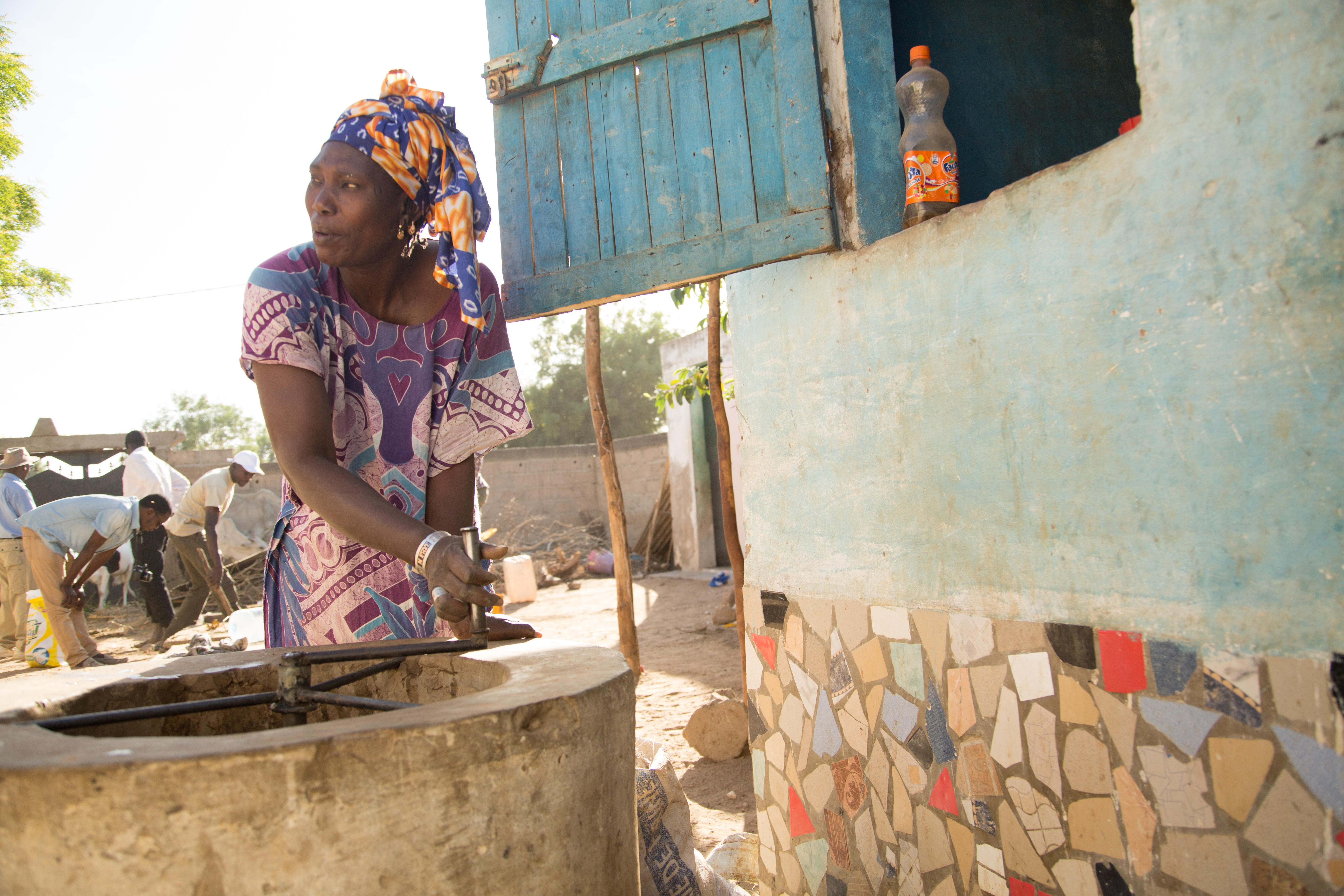 A woman outside in a colorful dress and headwrap turns the biodigester, a device with an underground tank that breaks down organic matter into fuel.