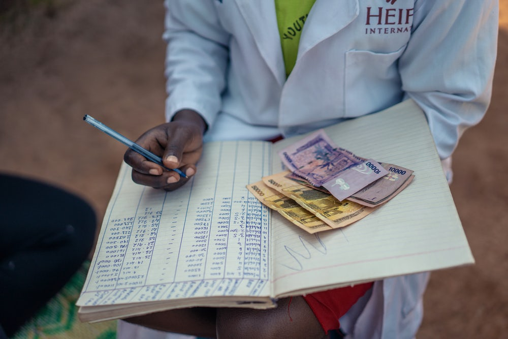 A Heifer coordinator writing in a ledger with money placed on the ledger.