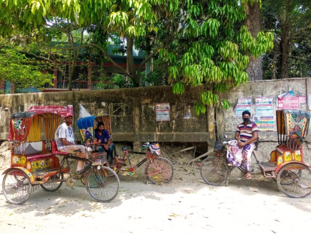 Rickshaw pullers wearing masks to protect themselves from COVID-19 virus.