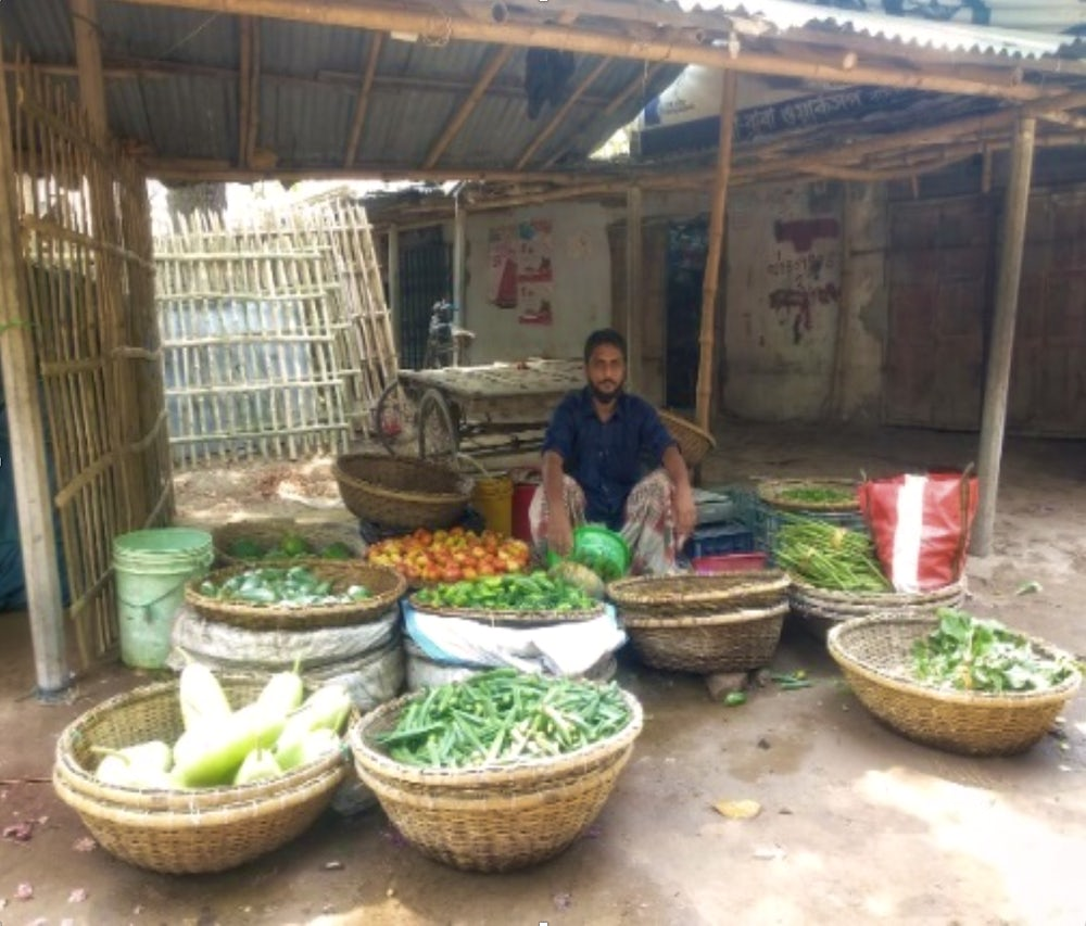 A man sits in a vegetable stall in Bangladesh, waiting for customers.