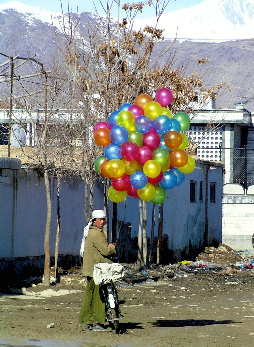 This man in Kabul travels through the neighborhoods of the city on his bicycle selling balloons to children.