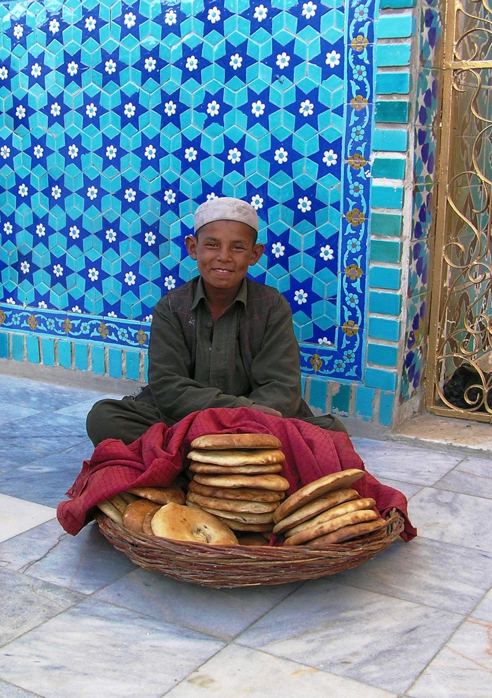 Young boy selling bread at the Blue Mosque in Mazar e Sharif. This round Afghan naan bread is typical of the northern part of the country. In Kabu, the bread is an elongated oval (caption and photos by David Sherman).