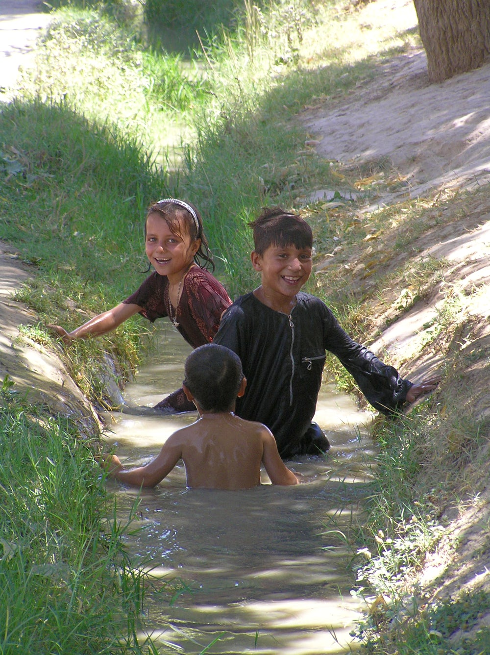 Children frolic and cool off in an irrigation canal on a blistering hot day in Balkh Province in a village outside of Mazar e Sharif.