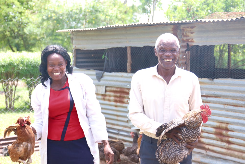 A Kenyan woman stands next to her dad in front of their thriving chicken coop.