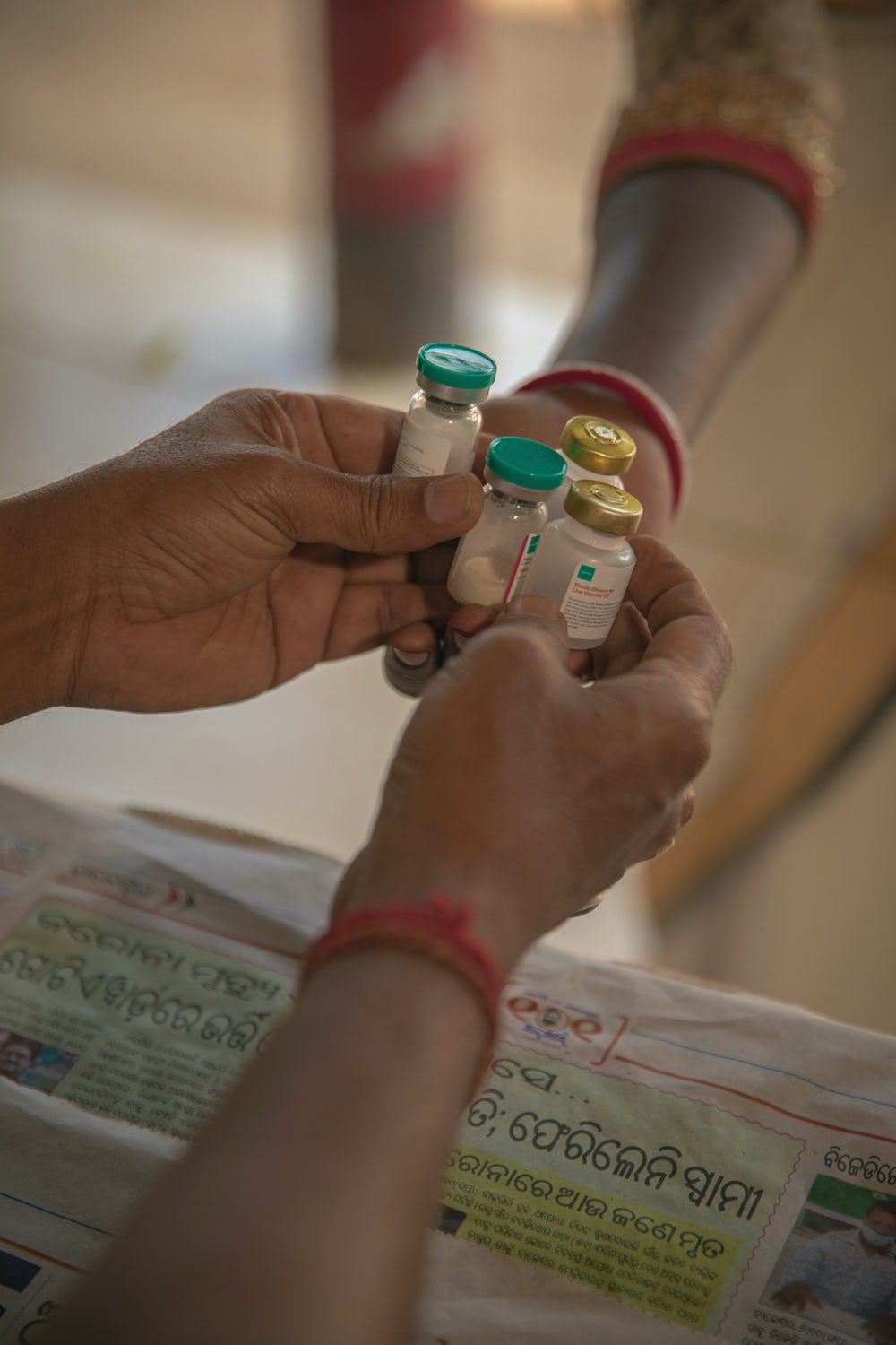 Vials of animal vaccines are handed to a vet's hand over a counter in India.