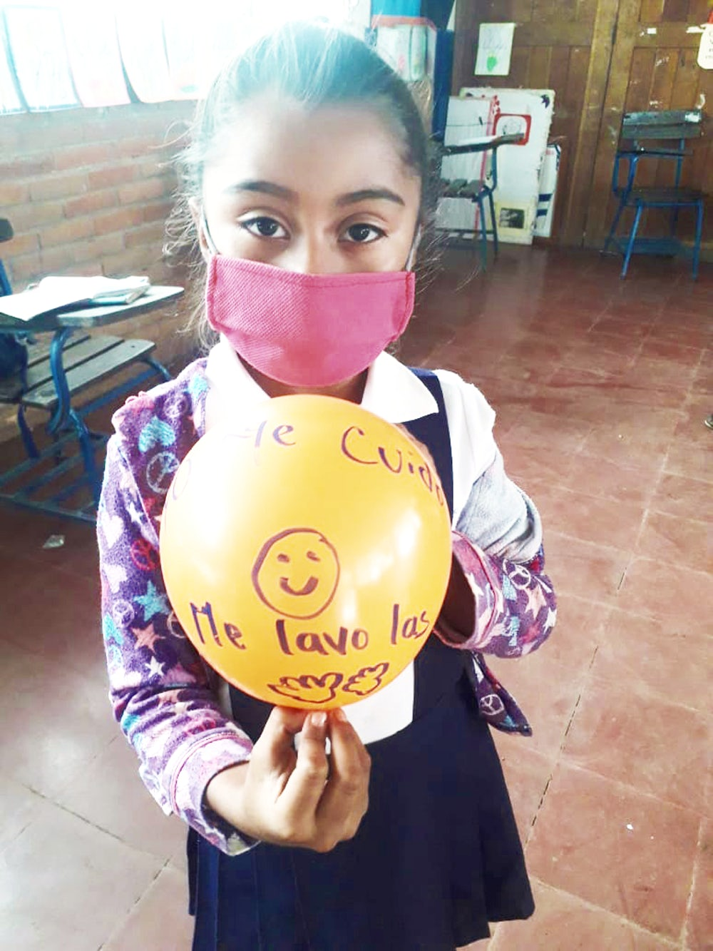 Young girl wearing a pink mask, holding a yellow balloon.