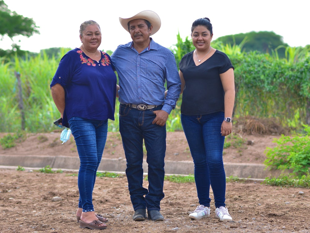 A cattle farming family poses for a photo in rural Mexico.