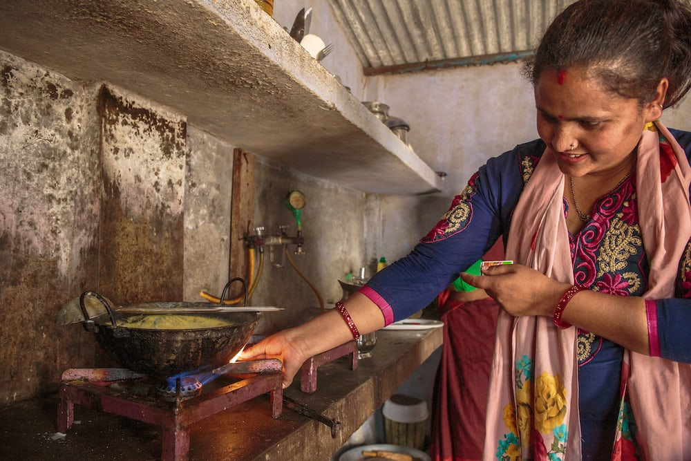 A smiling Indian woman lights her gas stove in her kitchen.
