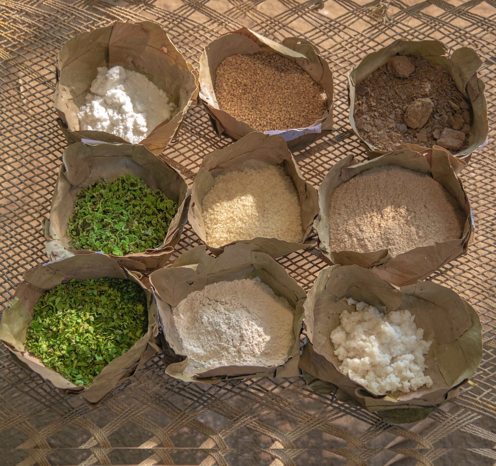 Nine components of a nutritious chicken feed sit in bowls.