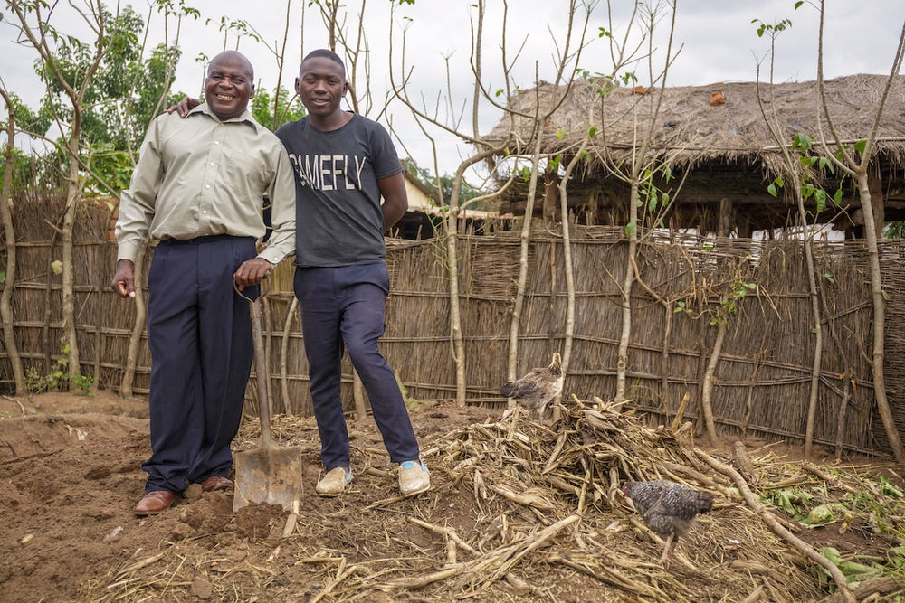 A father and son stand side-by-side on their compost pit in Malawi. Both are smiling and the dad holds a shovel in his hand.