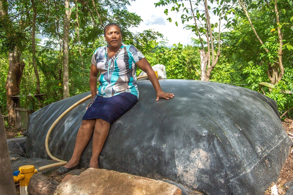 A Nicaraguan woman leans against a big grey dome in her backyard. The dome is a biogas unit.