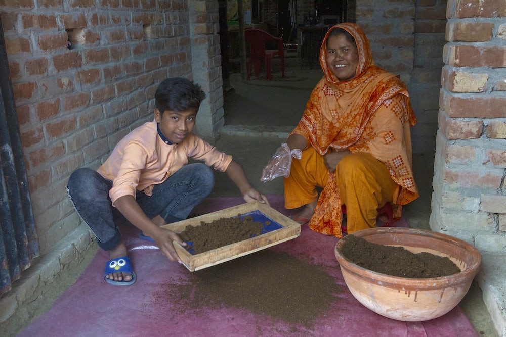 A woman and her nephew crouch next to a bowl full of vermicompost.