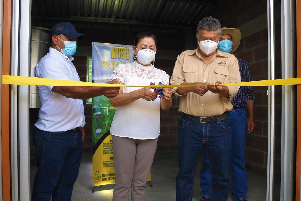 A woman and a man cut a yellow ribbon to mark the inauguration of a new honey processing plant.
