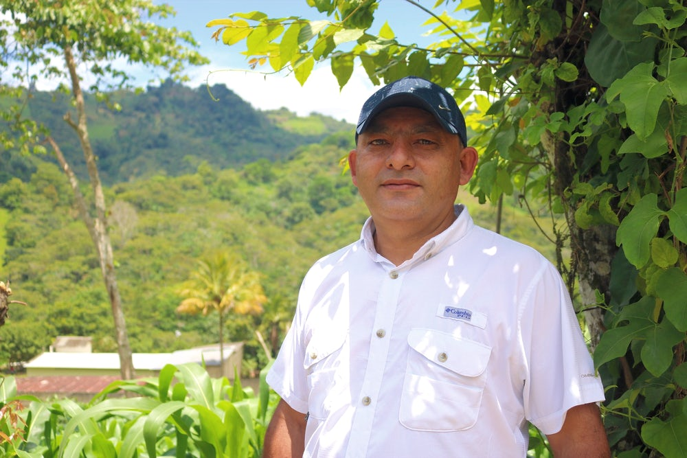 A male, Honduran beekeeper poses for a portrait in a hat and white shirt.