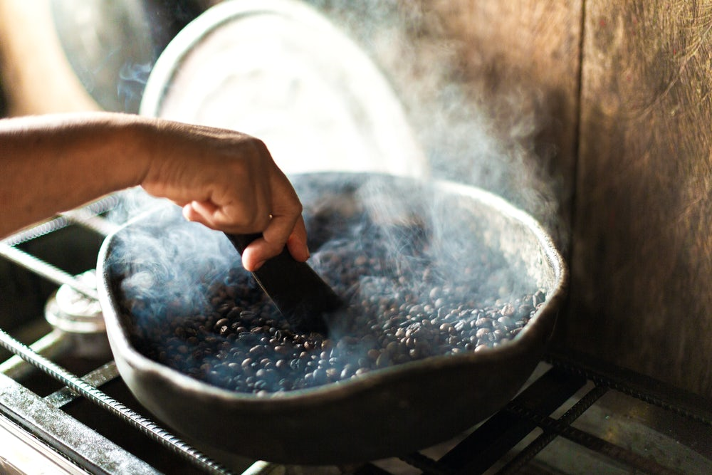 A close up shot of coffee beans roasting in a pan. A pair of hands uses a tool to mix them.