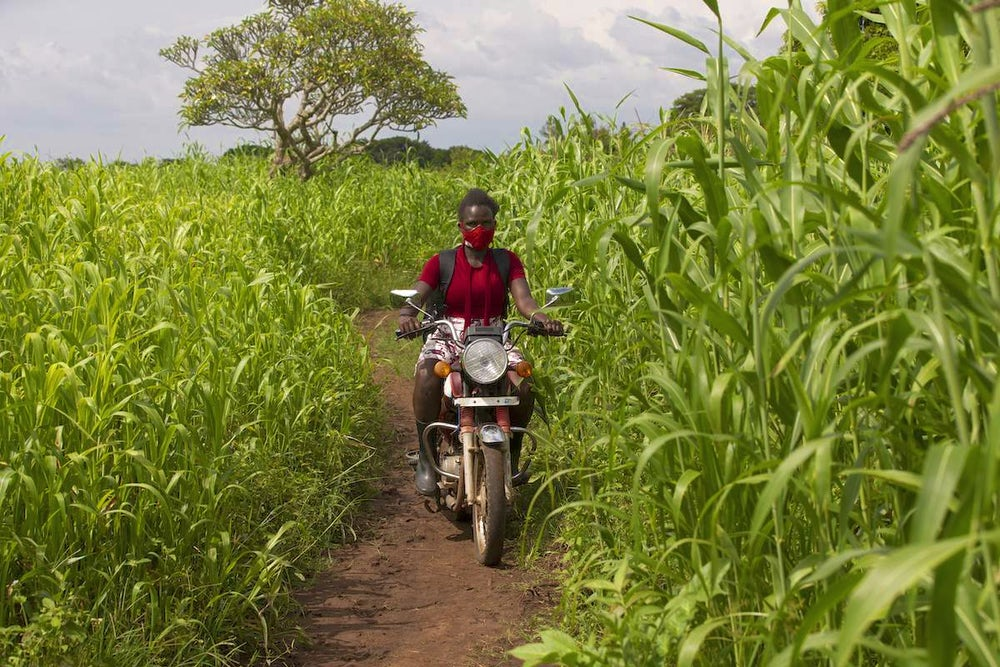 Amongi Leah travelling to farmers locations on her motorbike to deliver training.