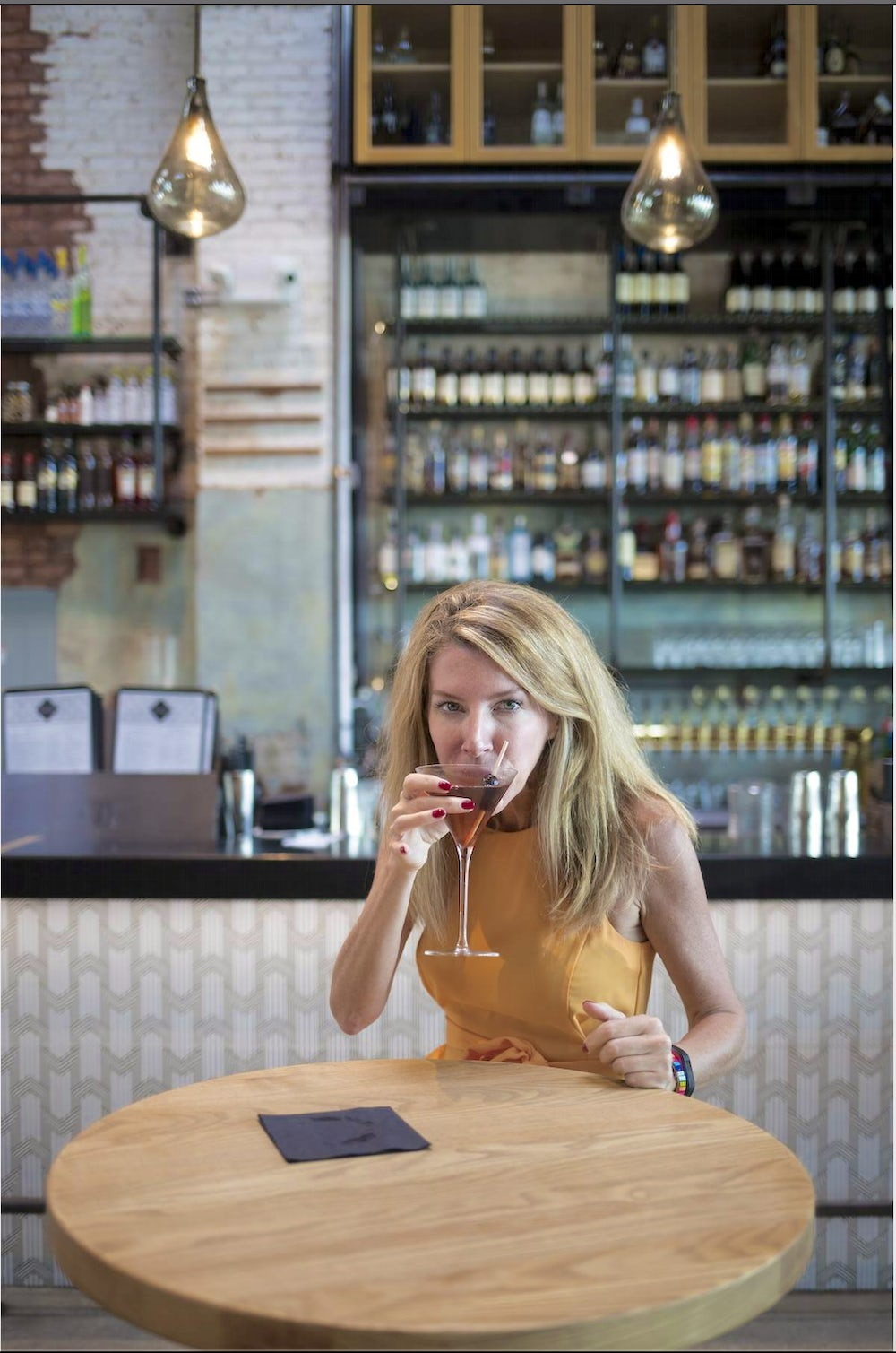 Laura Reiley sits at a bar table sipping a cocktail. She is wearing a yellow dress and looking directly into the camera over the rim of her glass.