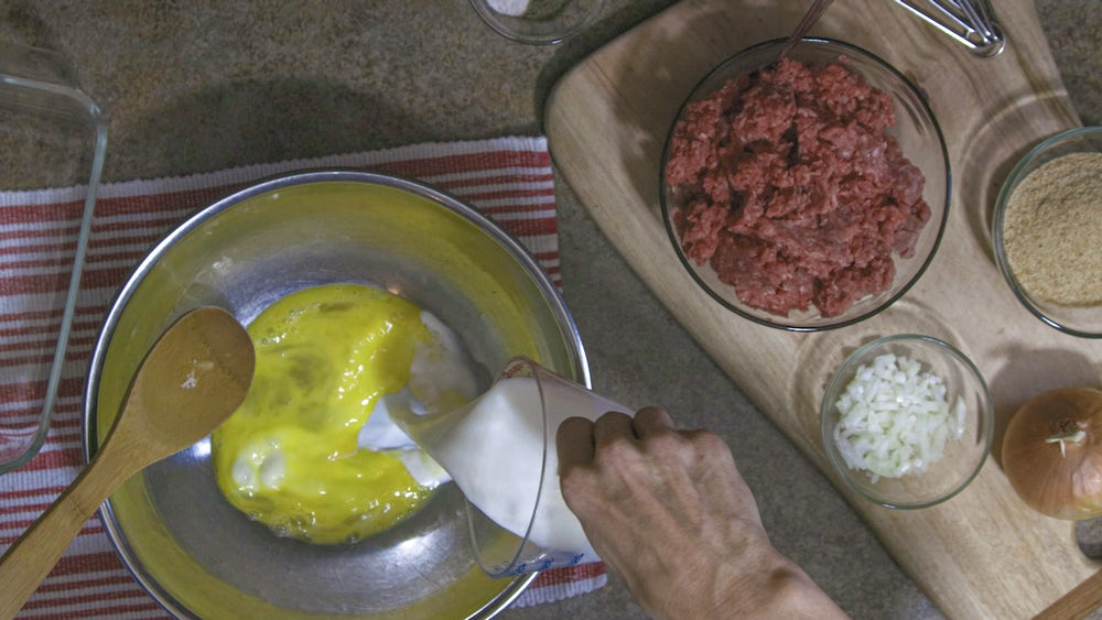 Liz Ellis mixes meatloaf ingredients together. You can see the full process in the video above!