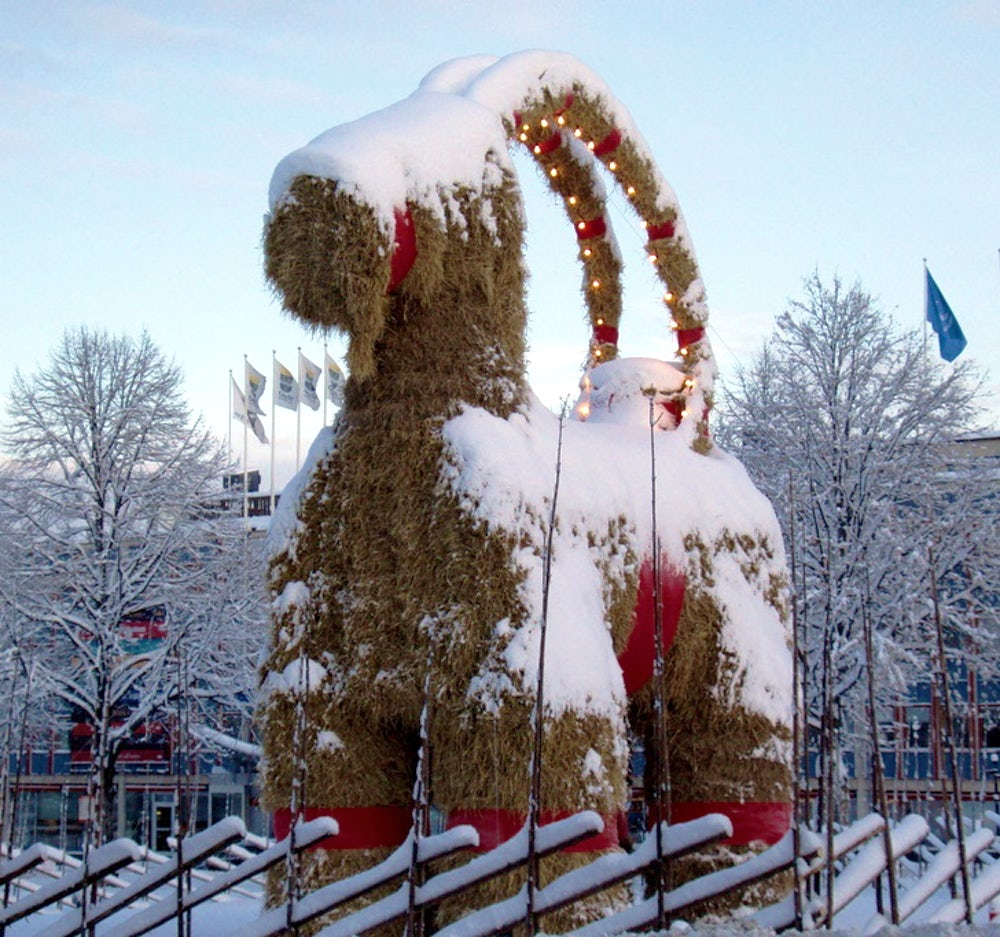 A giant, Yule goat made of straw, covered in snow.