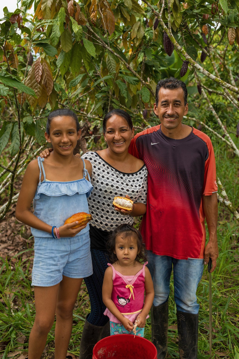 A family portrait in the chocolate grove of a man with his arm around his wife and older daughter, who are holding cacao pods, with the youngest daughter standing in front.