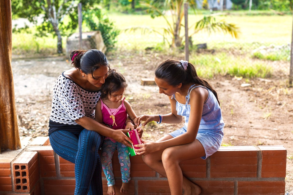 Digna Silva and her two daughters sit on a low brick wall, reading a book together.