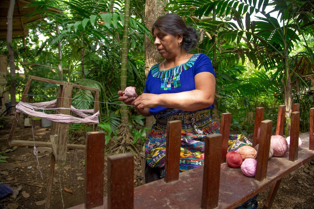 Rosalinda Tay sits outside her studio and winds yarn died with cochineal on her enrollado. In front of her is an urdidora or warping frame.