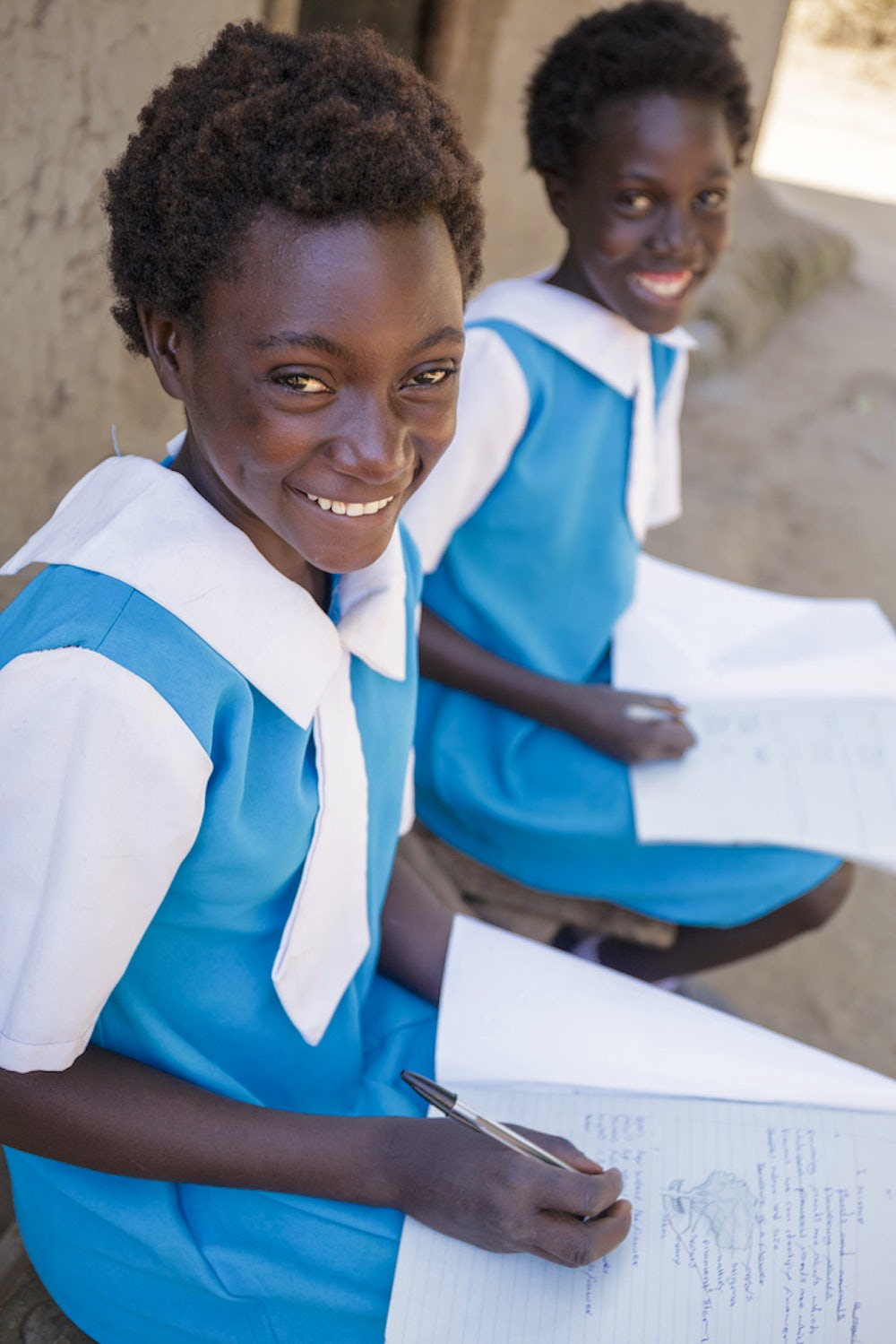 A 13 year old girl in a blue and white school uniform looks smiling while writing with a pencil on paper.