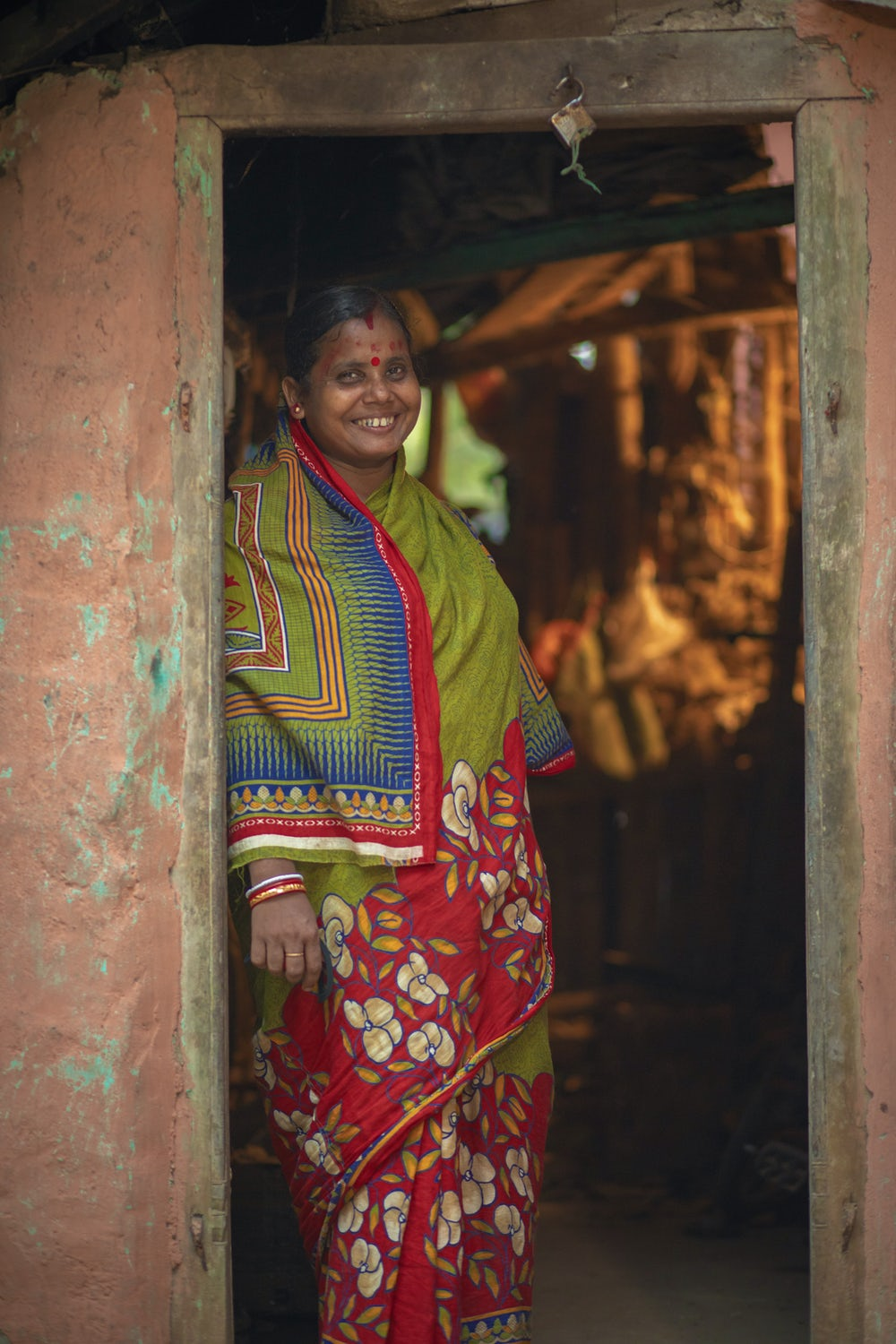 Geeta Rani Jena stands in the doorway of her home in Odisha, India.