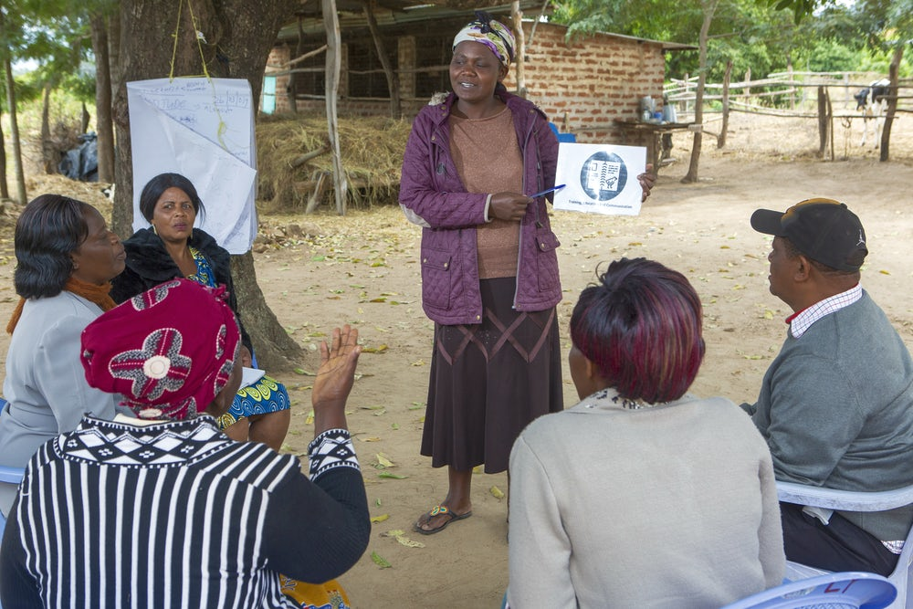 An african woman gives a presentation to a group of men and women outside of her home.