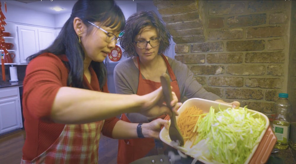 Annie Bergman Giattina Adds julienned vegetables to a hot wok while Pooi Yin Chong stirs.