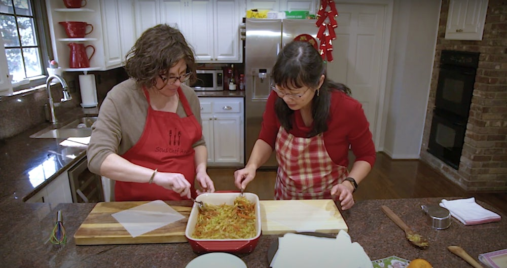 Two women in red aprons look over a pan of spring roll filling.