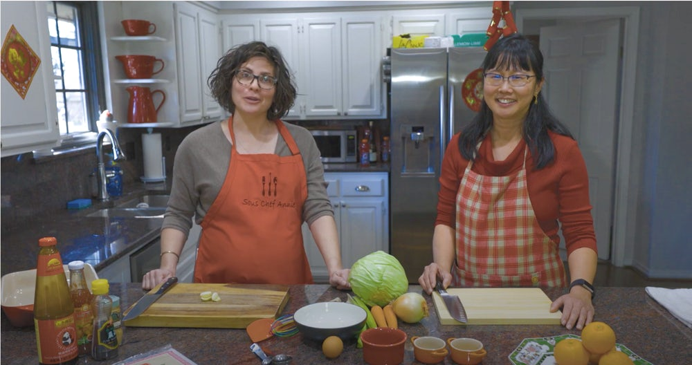 Two women, in red aprons, stand smiling for the camera. They are standing behind a kitchen island.