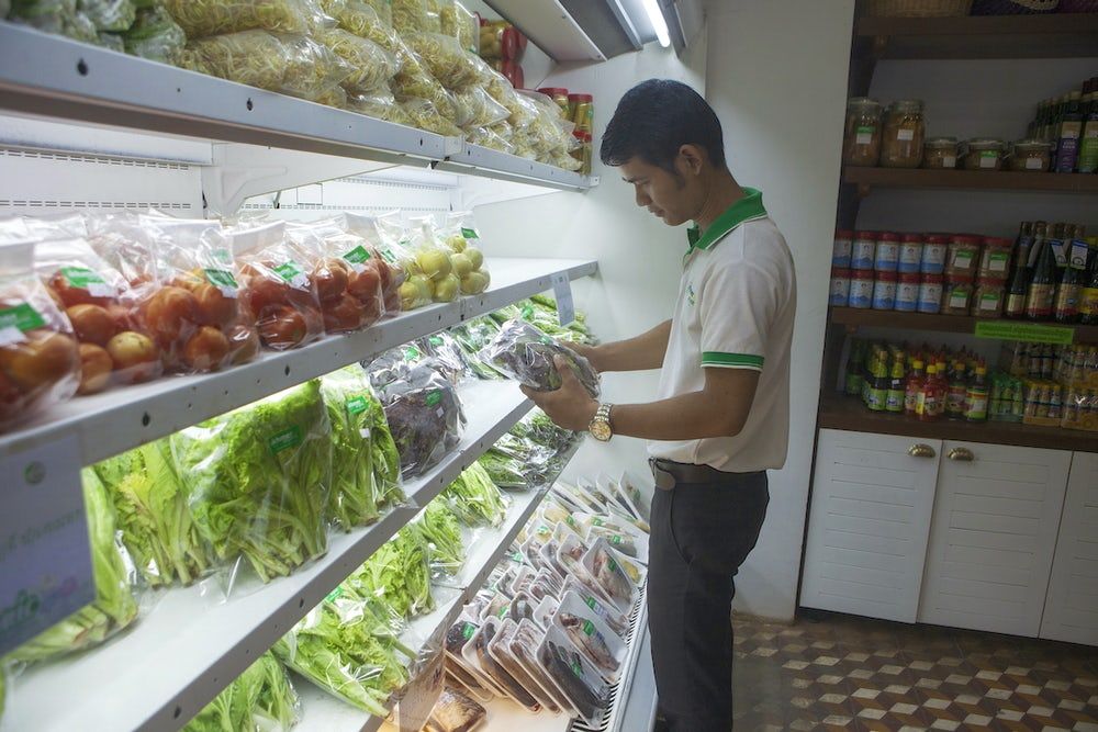 A Cambodian man stands in front of a refrigerated produce section of a local grocery store holding a fresh vegetable.