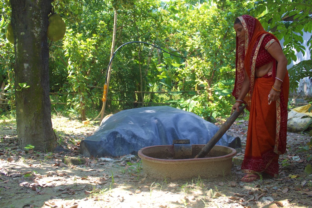 An Indian woman mixes a big wooden pot in her yard.