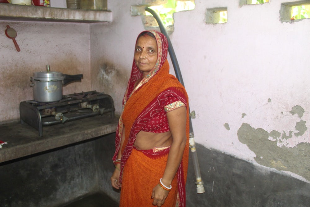 An Indian woman stands in front of her stove, looking at the camera.