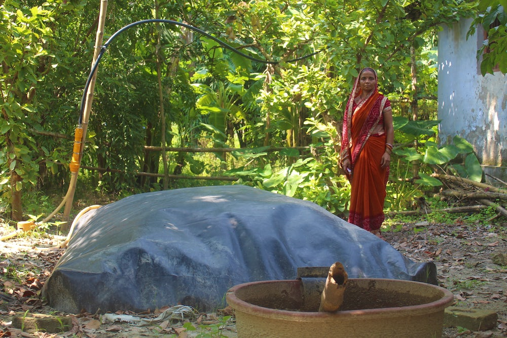 An Indian woman in orange dress stands behind her biodigester, a large grey dome on the ground.