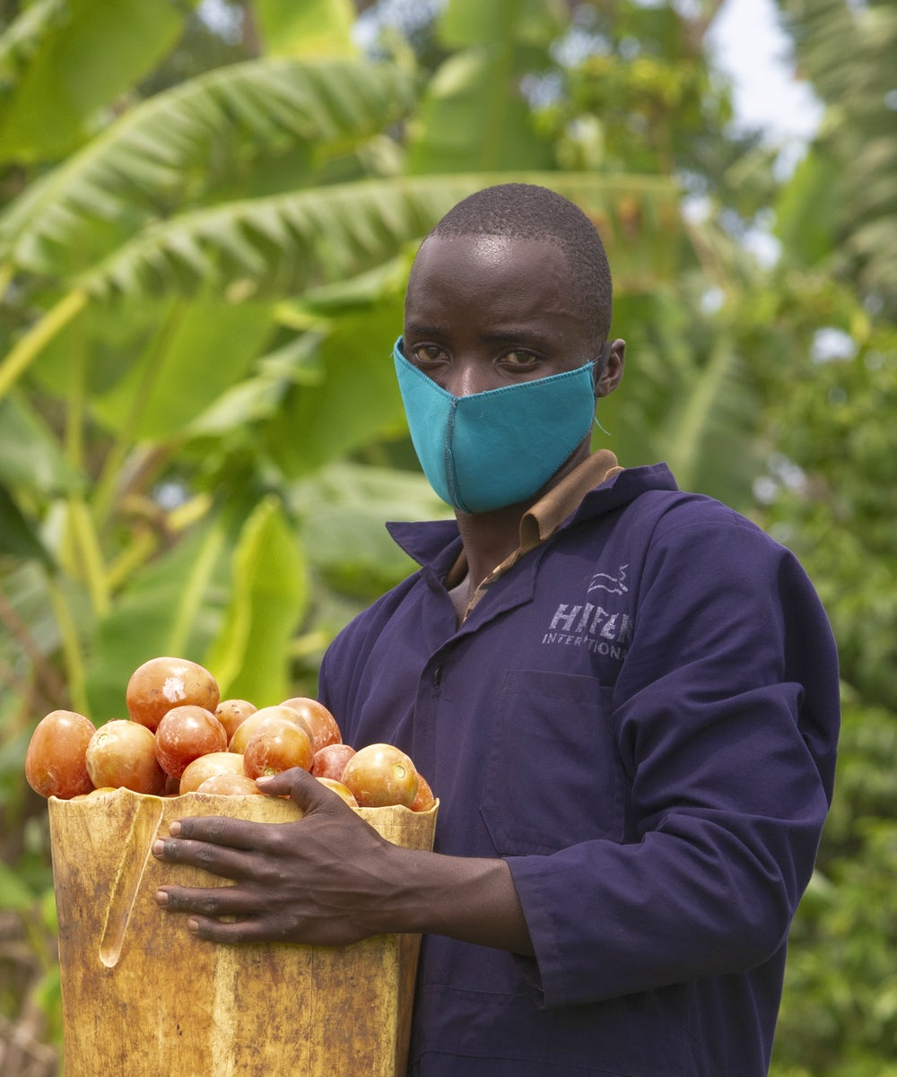 A young Ugandan man holds a basket of his tomatoes.