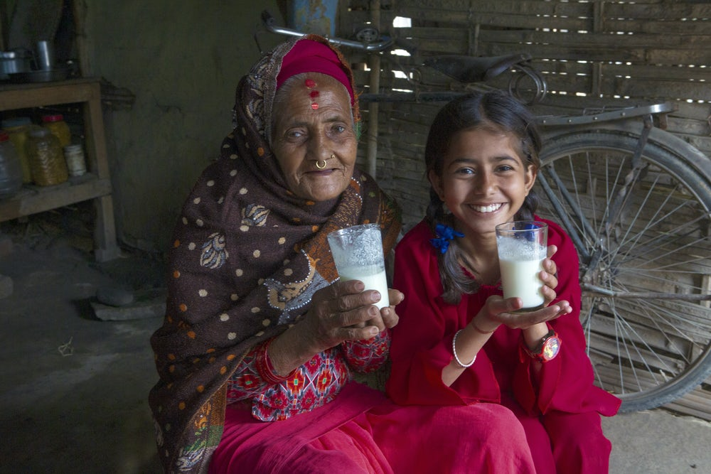 A smiling Nepali woman in her 70s and her 12-year-old granddaughter each hold a glass of milk in their hands.