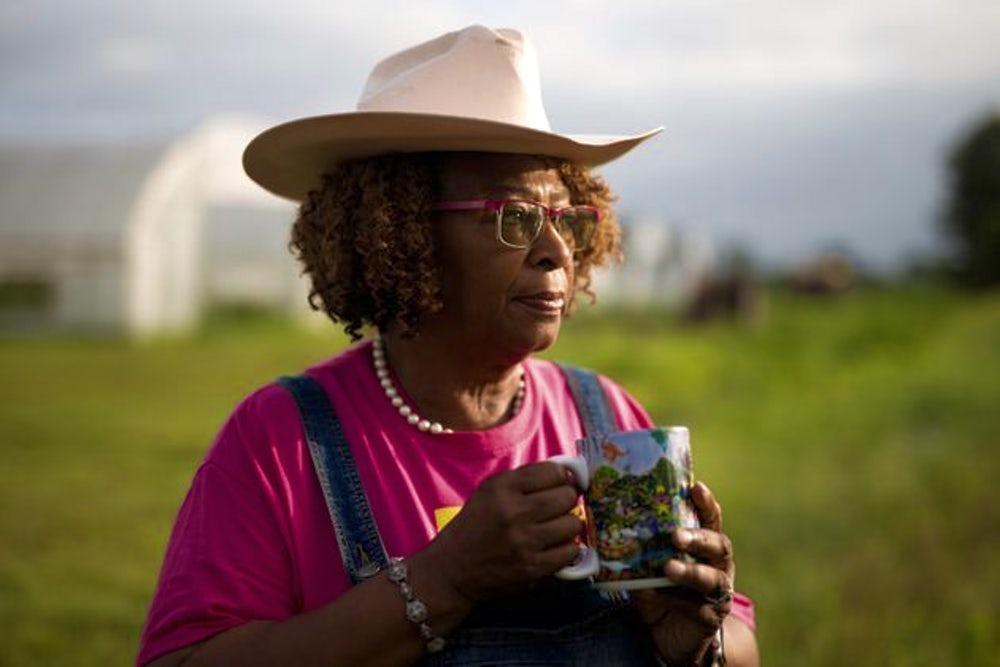 A woman wearing a hat and holding a coffee cup in her hands, stares into the distance.