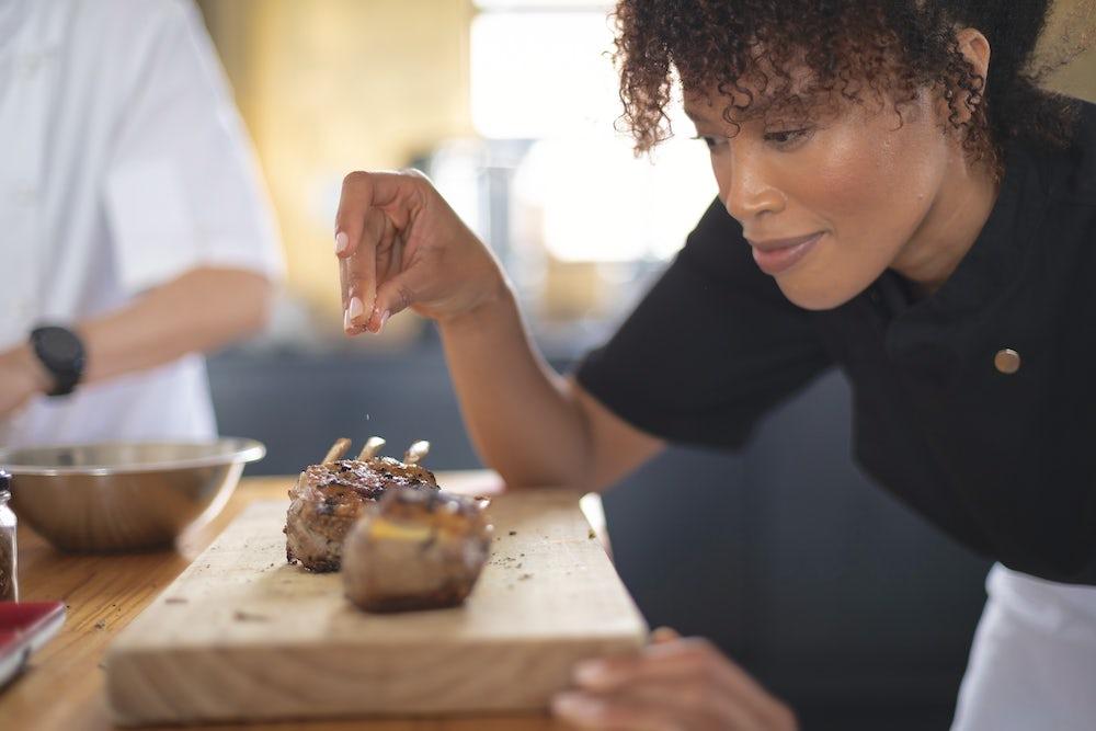 A woman chef seasons two lamb chops.