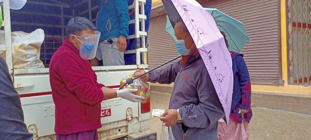 A community member exchanges money for a bundle of vegetables.