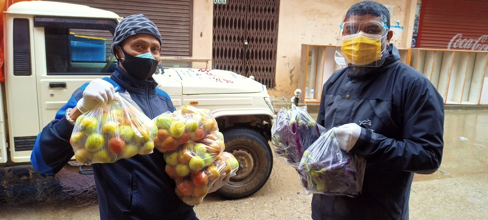 Two men wearing masks and face shields hold bags of produce.