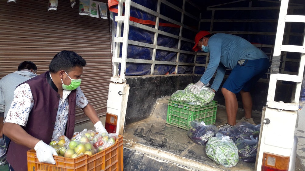 Two men wearing personal protective equipment load fresh vegetables into the back of a truck.
