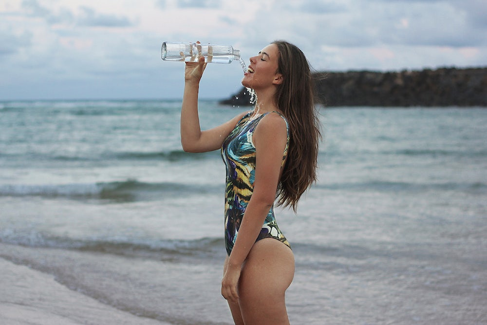 A woman stands on a beach  holding a water bottle up to her lips. She is letting water spill out of her mouth as if she's never consumed water from a bottle before, but really it's just for fashion.