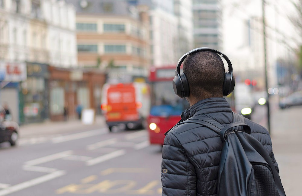 A man stands with his back to the camera near the crosswalk of a busy, city street. There are cars in the background of the picture and he is wearing headphones, a puff jacket and a backpack.