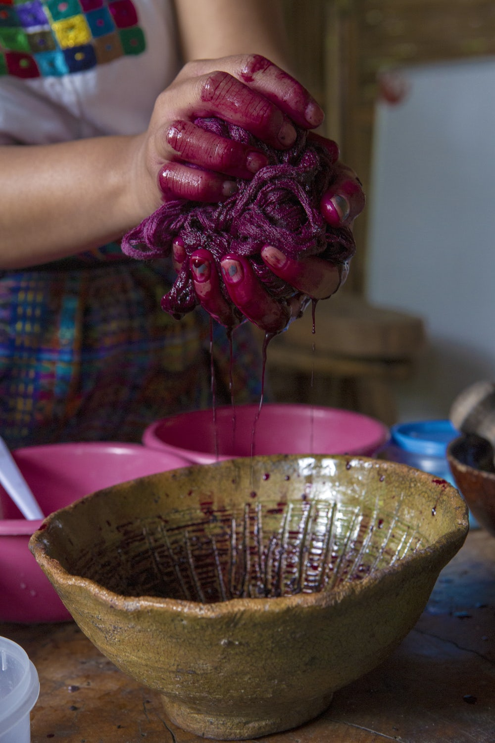 Close up of hands squeezing excess red carmine dye from a skein of cotton yarn