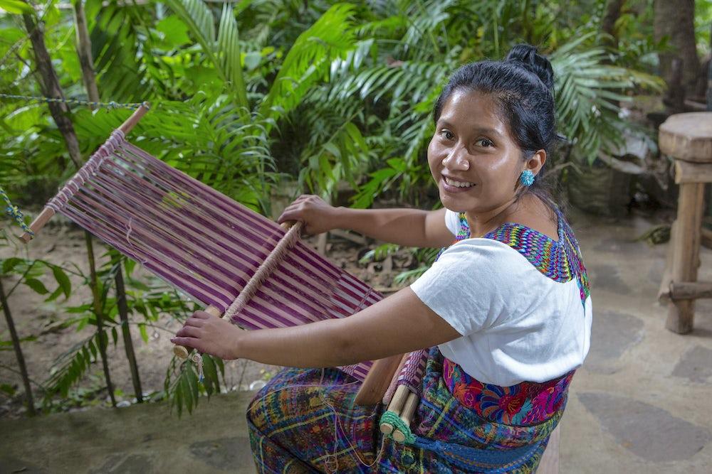 A woman sits at a backstrap loom weaving a shawl with various shades of crimson. She is smiling at the camera.