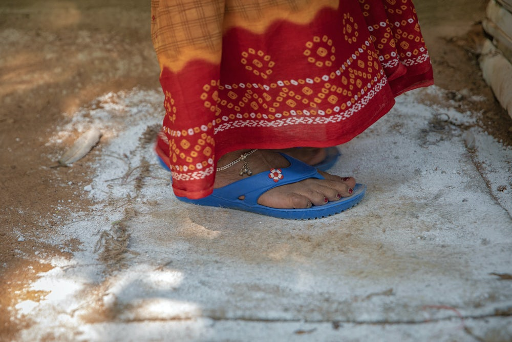 A close up shot of a woman's feet standing on a mat coated in lime, a dusty white powder.