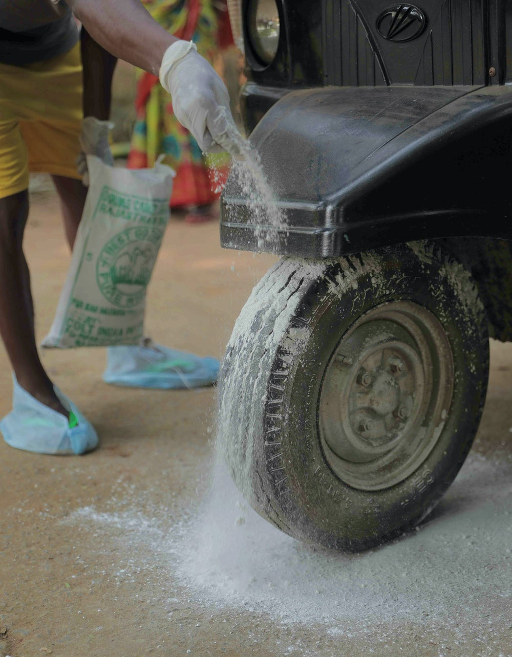 A man dusts a white powder, lime, onto his vehicle's wheels.